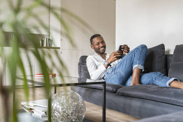 Portrait of smiling man sitting on couch in modern apartment using smartphone - AHSF02768