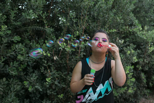 Teenager girl with down syndrome wearing 80's colorful make-up and clothes blowing soap bubble - DCRF00296