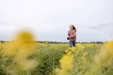 Smiling girl in pink coat running by rape field - EYAF01124