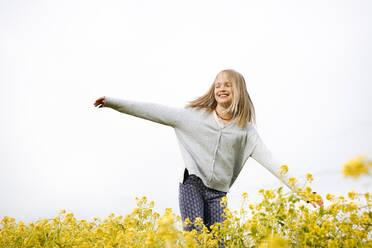 Smiling girl walking on rape flowers - EYAF01130