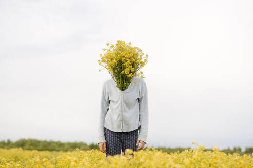 Portrait of girl covering her face with bouquet of rape flowers - EYAF01133