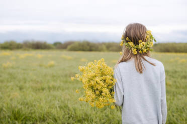 Rear view of girl with wreath and rape flowers - EYAF01139