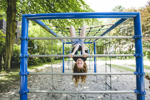 Smiling girl hanging upside down on jungle gym in playground at park - IHF00354