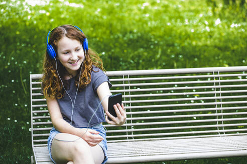 Smiling girl taking selfie through smart phone while sitting on bench at park - IHF00357