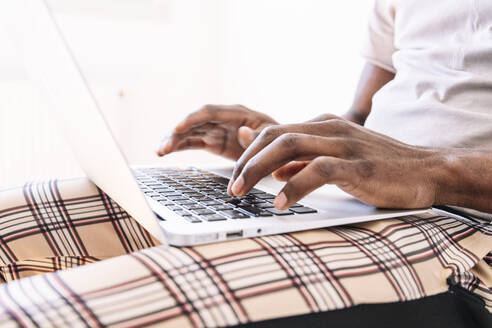 Young businessman typing on laptop while working at home - JCMF00837