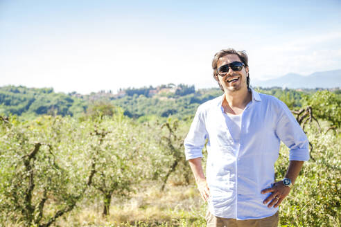 Happy mid adult man standing with hands on hip at olive plantation against sky during sunny day - FLMF00234