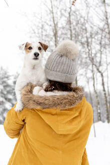 Rear View Of Woman In Warm Clothing Carrying Dog In Snow Covered Forest - EYF05597