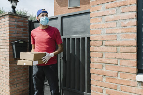 Mid adult male delivery person looking away while holding package and standing against house gate - XLGF00188