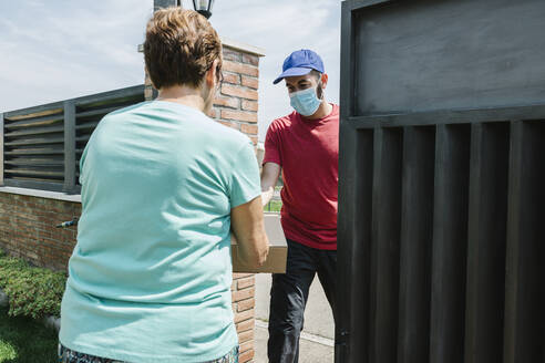 Senior woman receiving delivery package from postal worker at gate - XLGF00191
