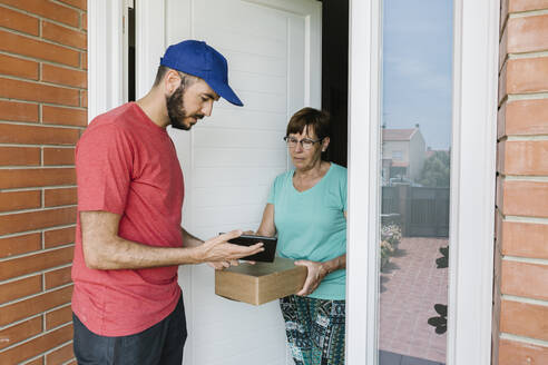 Postal worker showing digital tablet to senior woman for signature at doorway - XLGF00200