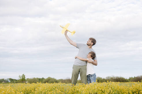 Smiling boy embracing father holding toy airplane on oilseed rape field against sky - EYAF01147