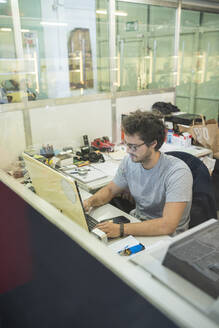 Young businessman using computer while sitting in illuminated office - MTBF00436