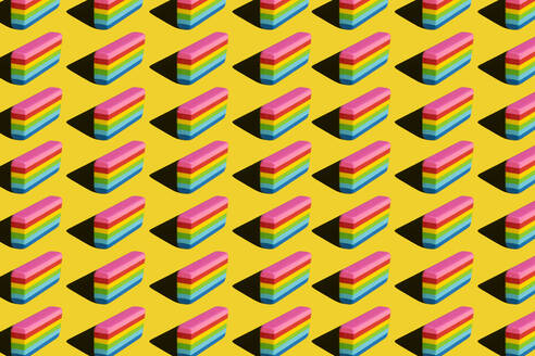 Pattern of rainbow colored erasers against yellow background - XLGF00204