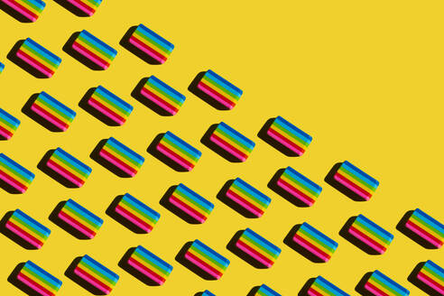 Pattern of rainbow colored erasers against yellow background - XLGF00207