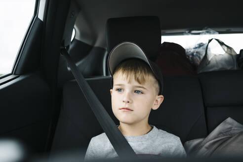Cute boy looking away while sitting in car - JVSF00001