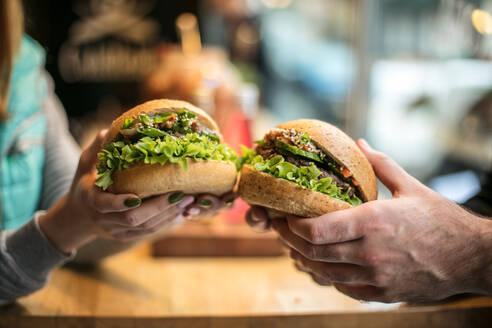 Close-Up Of Couple Holding Hamburgers - EYF05992