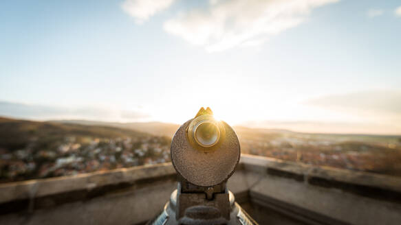 Close-Up Of Coin-Operated Binoculars Against Cityscape During Sunset - EYF06232