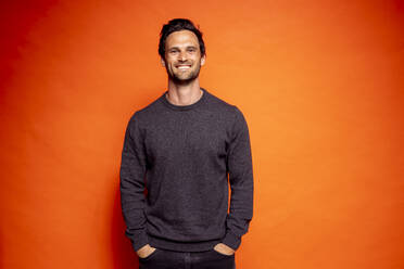 Happy handsome man with hands in pockets against orange background - DAWF01598