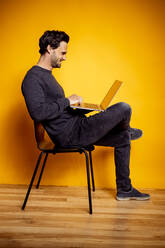 Smiling man using laptop while sitting on chair by yellow background - DAWF01616
