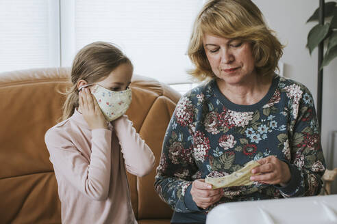 Girl wearing homemade protective face mask while sitting by grandmother at home - VBF00101