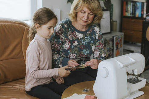 Girl cutting textile held by grandmother while making face mask at home - VBF00104