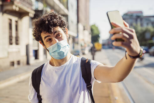 Close-up of young man wearing mask taking selfie with smart phone while standing in city - MEUF00921