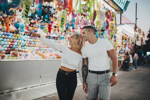 Happy woman pointing at stall while standing with boyfriend in amusement park - MIMFF00067