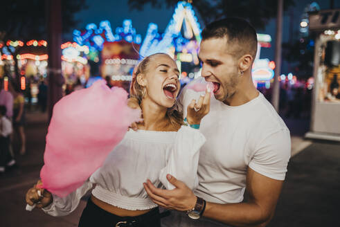 Cheerful young woman feeding cotton candy to boyfriend at amusement park - MIMFF00070