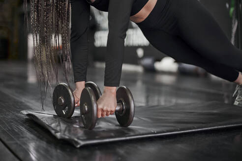 Close-up of female athlete holding dumbbells while exercising on mat in gym - VEGF02350