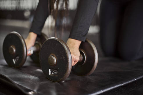 Close-up of young woman holding dumbbells on mat in gym - VEGF02353