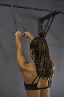 Female athlete with braided hair exercising with resistance band in gym - VEGF02392