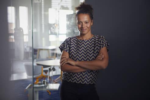 Portrait of smiling businesswoman in modern office - RBF07729