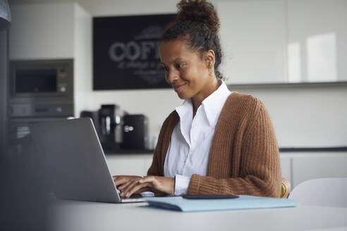 Smiling businesswoman sitting at table in kitchen using laptop - RBF07753