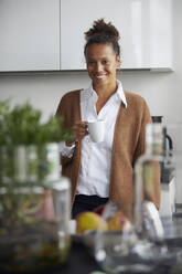 Portrait of smiling businesswoman standing in kitchen with cup of coffee - RBF07756