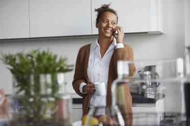 Portrait of smiling businesswoman on the phone standing in kitchen with cup of coffee looking at distance - RBF07759