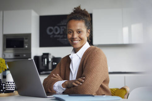 Portrait of smiling businesswoman with laptop sitting at table in kitchen - RBF07762