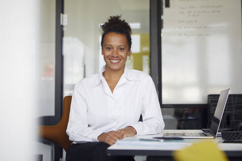 Portrait of smiling businesswoman sitting at desk in office - RBF07765