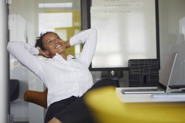 Portrait of happy businesswoman relaxing at desk in office - RBF07768