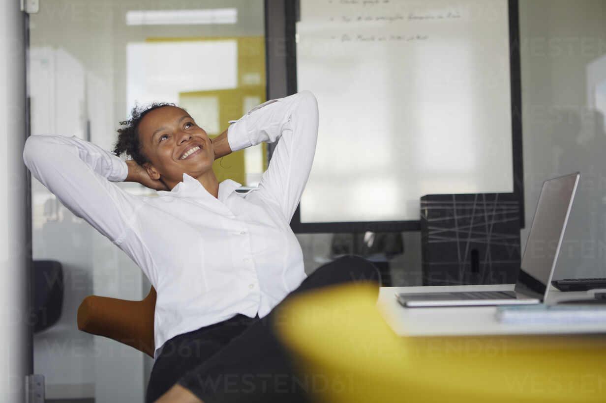 Portrait of happy businesswoman relaxing at desk in office - RBF07768 - Rainer Berg/Westend61