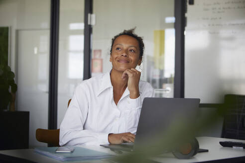 Portrait of smiling businesswoman sitting at desk in office looking at distance - RBF07771