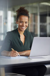 Portrait of smiling businesswoman working at desk - RBF07774