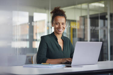 Portrait of smiling businesswoman working on laptop at desk - RBF07777