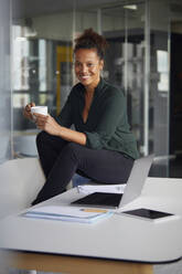 Portrait of smiling businesswoman sitting on desk with cup of coffee having a break - RBF07780