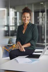 Portrait of smiling businesswoman sitting on desk in office - RBF07783