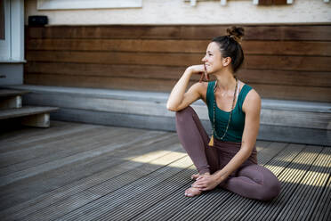 Thoughtful smiling woman looking away while sitting on hardwood floor against house - DAWF01625
