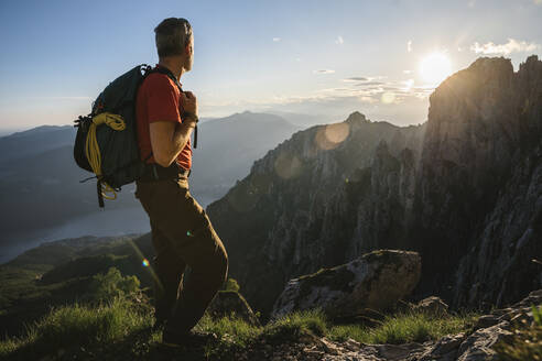 Male hiker with backpack looking at mountains during sunset, Orobie, Lecco, Italy - MCVF00451