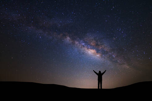 Silhouette Man With Arms Raised Standing Against Star Field At Night - EYF07045