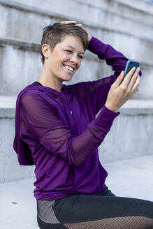 Athletic woman using smartphone and taking a selfie - LVVF00090