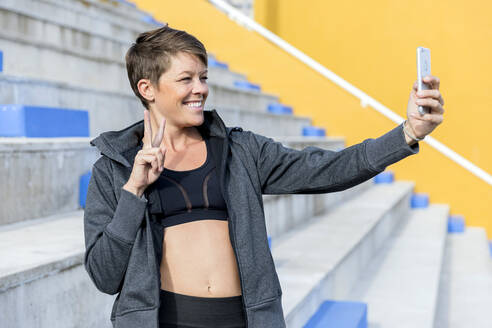 Athletic woman using smartphone and taking a selfie - LVVF00099