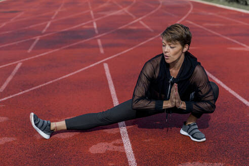 Sportive woman stretching on tartan track - LVVF00105